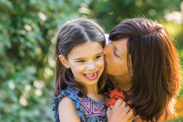 The Vital Science podcast episode 01 is an image of Julia Vitarello kissing her daughter Mila on the cheeck, as both smile.