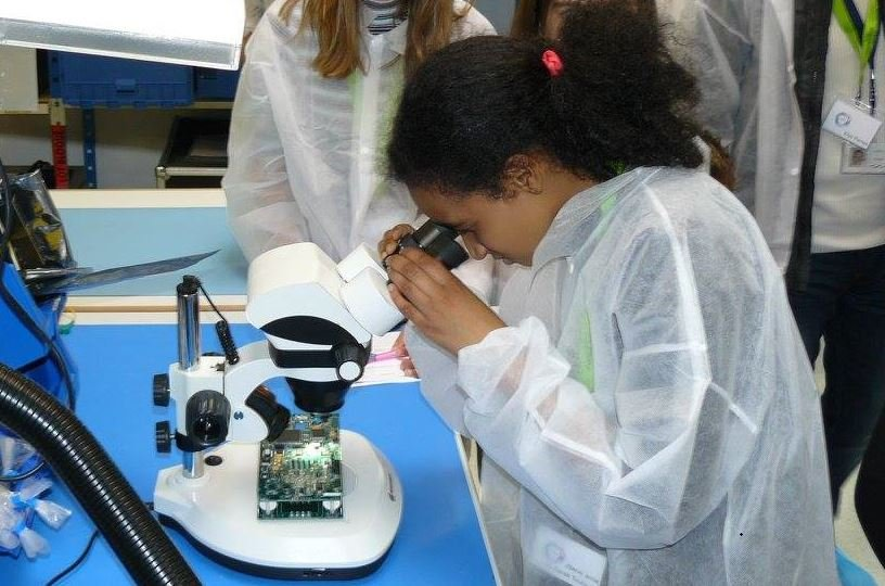 Young girl at microscope at educational event